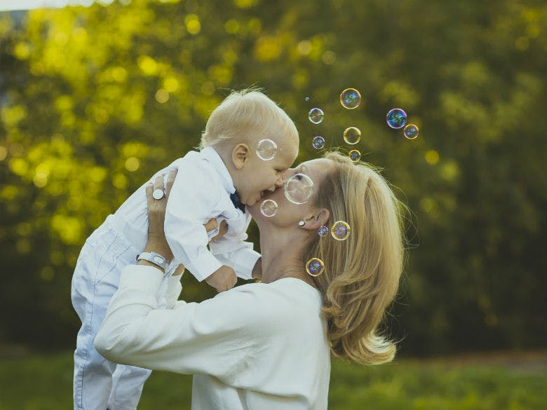 happy-son-with-mother-in-garden-and-soap-bubbles