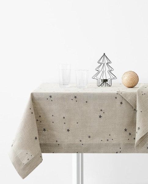 Tela em branco | Não é em branco mas é em cru - e vem com umas estrelinhas! Apostar numa toalha com cores menos folclóricas deixa-nos espaço para ousar mais na decoração da mesa. | Toalha de mesa Zara Home, 59,99€