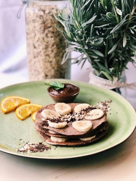 Panqueca proteica de chocolate com banana, amêndoa e creme de avelã e cacau