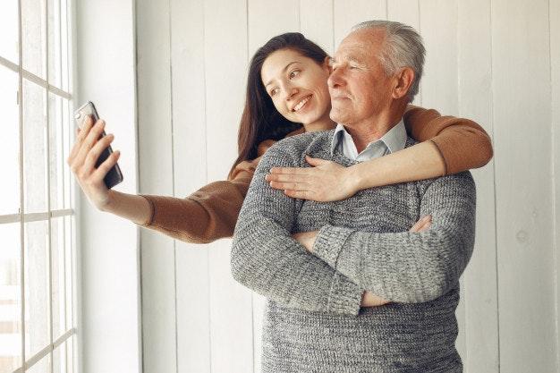 Elegante anciano para en su casa con su nieta