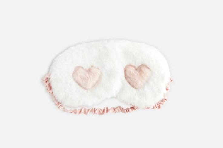 Antifaz de pelo en color blanco con detalle de corazones rosas de Oysho